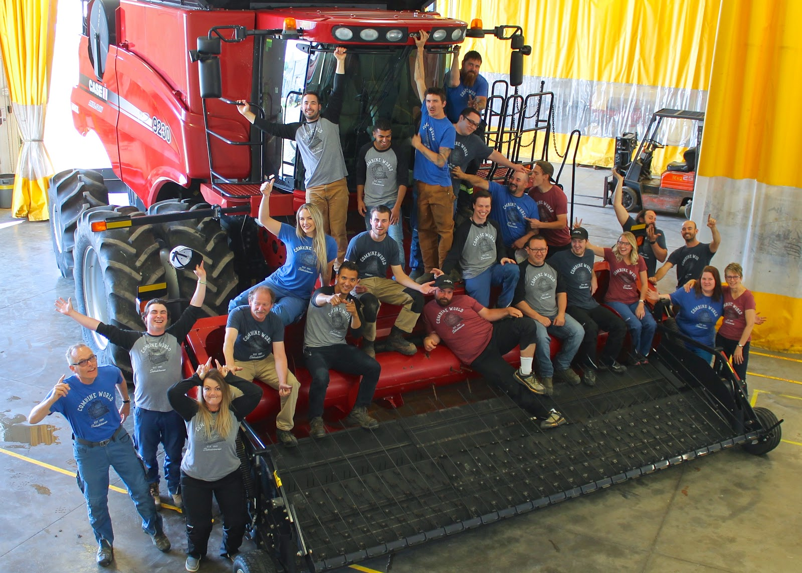 Combine World Team Picture from 2018. About two dozen people sitting on the front of a Case 9230 combine, pulling funny faces & gestures. It's a fun workplace.