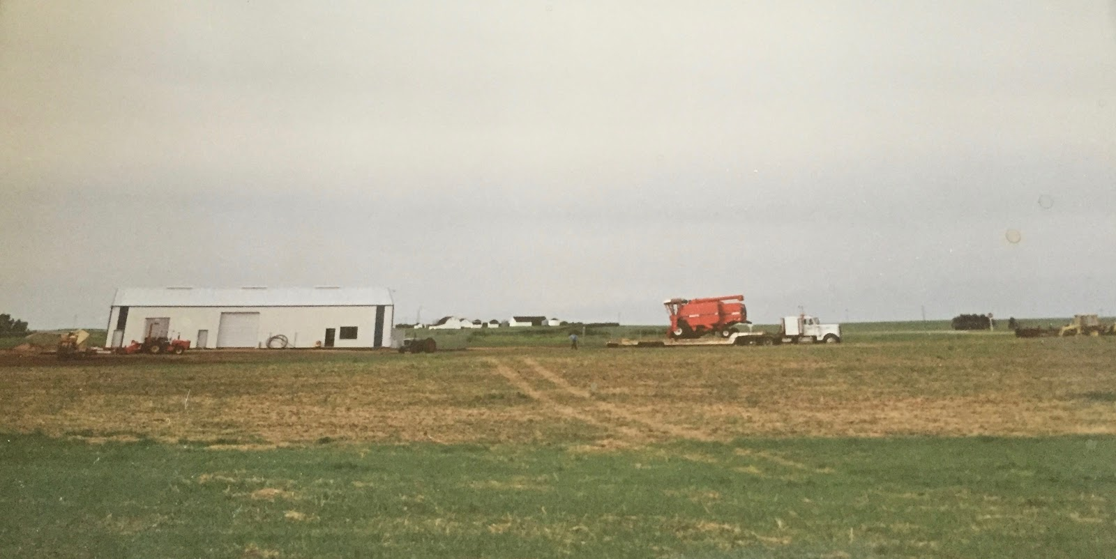 The Elstow/Saskatoon location of Combine World in 1994. A White 8900 combine is being hauled by a white semi into an open field, a tiny human figure directing it. At left, Combine World's main office for many years, Building #1